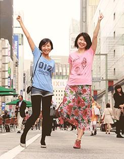 """画像:河野さん(左)と島野さんによる「あがせガール」。""""ユニホーム""""は、県内共通の市外局番をアピールする「017Tシャツ」と、下北・津軽・南部をイメージさせるモチーフを盛り込んだ「ビーナスTシャツ」"""